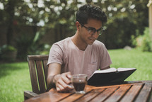 a young man reading a Bible in his backyard
