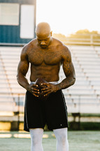a shirtless man holding a football on a sports field