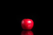 A red apple set against a black background.