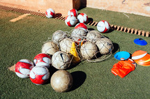 Soccer balls and equipment on a soccer field.