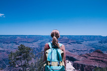 a woman with a backpack standing at the edge of a cliff
