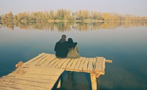 a couple sitting at the end of a dock