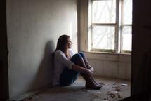 teen girl sitting alone in an empty room