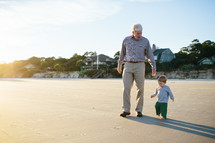 grandfather and grandson walking on a beach