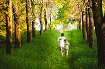 Two boys walking along a path of green grass lined by trees.