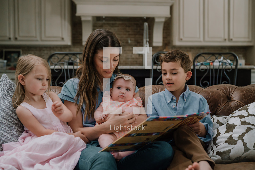 a mother reading a children's book to her kids