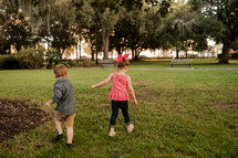 children walking through the grass at a park
