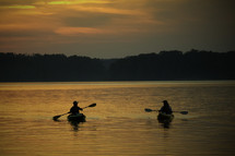 silhouettes of kayakers paddling at sunset
