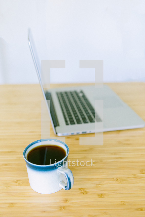 Coffee and laptop in background