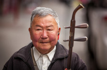 an elderly man holding an stringed instrument