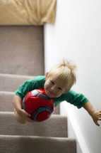 toddler boy walking up steps holding a soccer ball