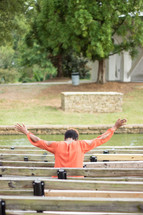 a woman with raised hands sitting in a bench outdoors