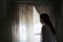 a young woman looking out a window