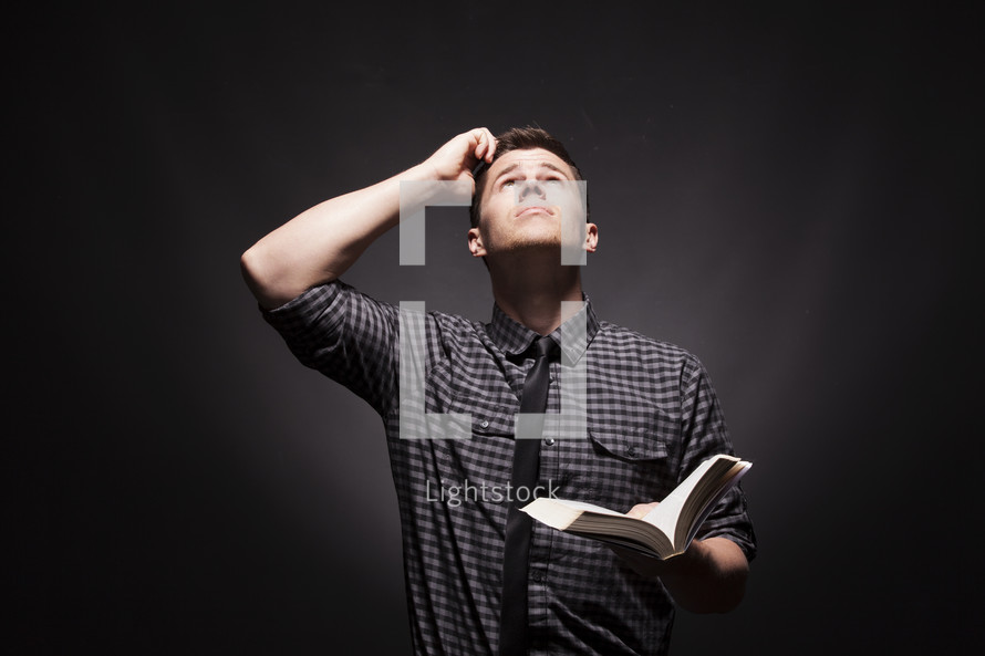 Puzzled man holding a Bible, looking to the heavens scratching his head.