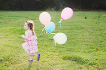 girl child running with balloons