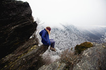 a woman sitting on a rock on a winter mountain
