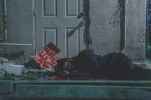 homeless man sleeping on a sidewalk