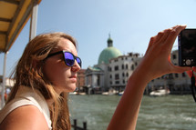 woman taking a picture with a camera from a boat in Venice