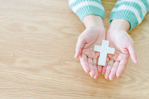 a cross in cupped hands