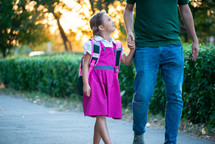 child walking to school holding dad's hand
