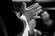priest with praying hands