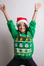 woman in an ugly Christmas sweater and santa hat celebrating