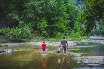 family walking in a stream bed