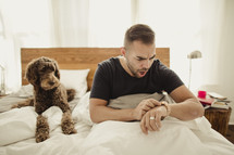 Man waking up late, in bed with dog.