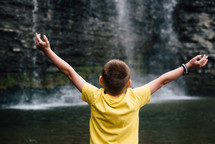 a child with outstretched arms standing in front of a waterfall