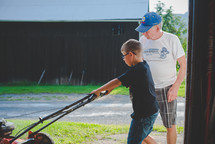 grandfather and grandson working on a lawnmower