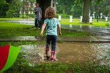 toddler playing in a puddle
