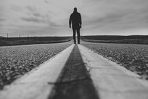 a man walking down the middle of a road