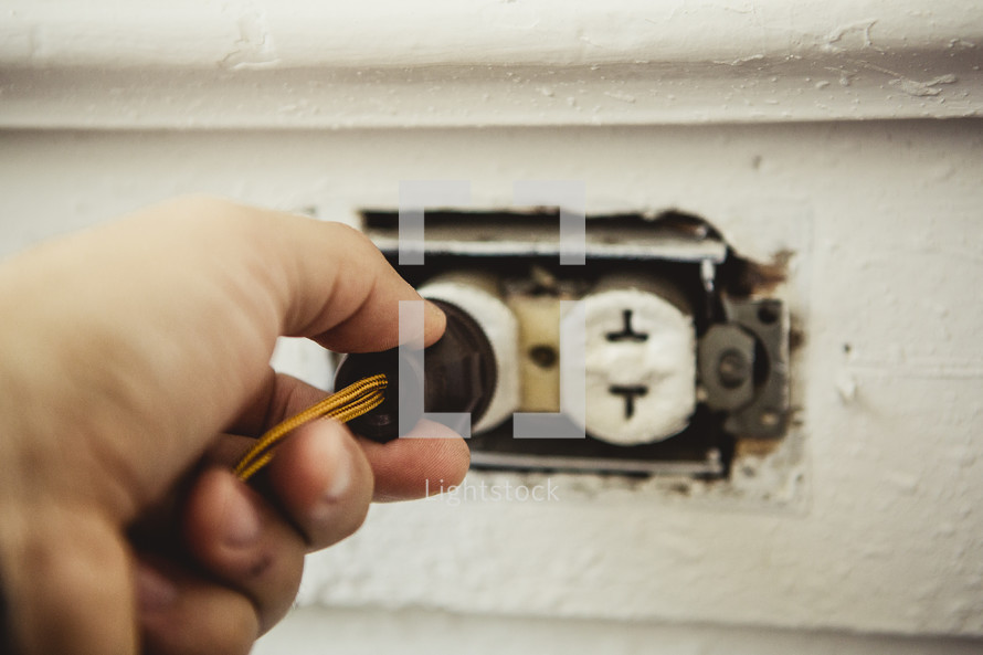 Hand holding plug in electrical outlet in wall.