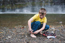 a child taking off his shoes to roll up his pants and play in a stream