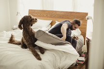 Man rising out of bed with dog.