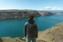 a man standing at the edge of a cliff and looking over into the water