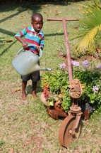 a child watering a flower bed