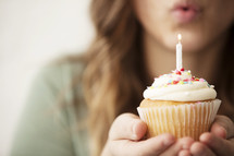 A woman blowing out a candle on a birthday cupcake