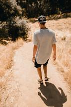 a man walking on a dirt path