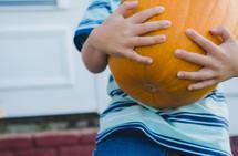 a child carrying a large orange pumpkin