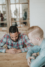two men sitting at a table praying together