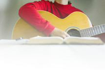 a person reading a Bible and playing a Guitar
