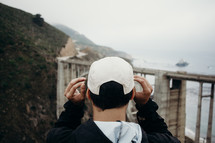 man, looking at a bridge connecting two mountains near the ocean