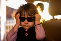 girl wearing sunglasses in a car