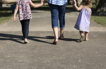 mother and daughters holding hands at a park