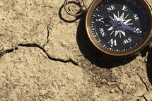 A  compass on a cracked, bare ground.