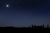 silhouettes of shepherds with herd starting to follow the star of Bethlehem.