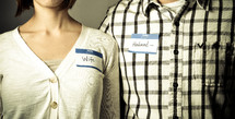 """Couple wearing """"husband"""" and """"wife"""" name tags"""