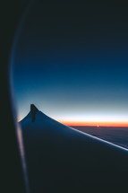 wing of a plane through a window at dawn
