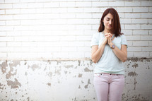 a young woman with praying hands standing in front of a white wall